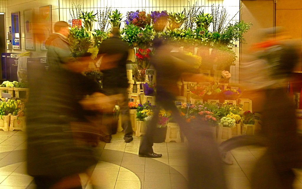 Photo: Flower stall with blurred streaks of people rushing by.